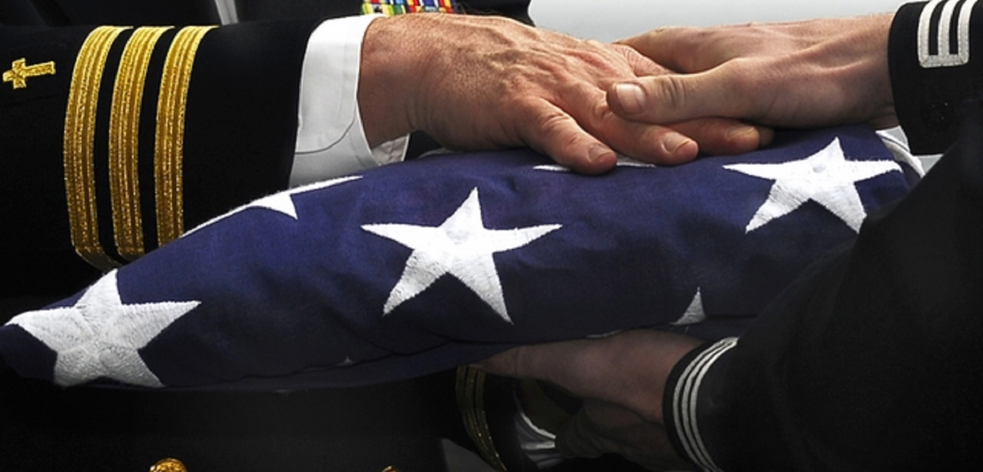 U.S. Navy Cmdr. Ronald Kawczynski hands a U.S. flag to Religous Program Specialist 3rd Class David Swan during a burial-at-sea aboard the aircraft carrier USS John C. Stennis (CVN 74) Feb. 16, 2009, in the Pacific Ocean.  The ship is on a scheduled six-month deployment to the Western Pacific. (U.S. Navy photo by Mass Communication Specialist 3rd Class Walter M. Wayman/Released)